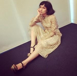 黄色いシースルーのワンピースを着て座っている佐田真由美の画像