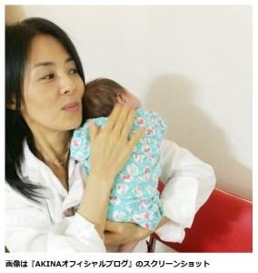 赤ちゃんの様子を伺いながら抱っこする井森美幸