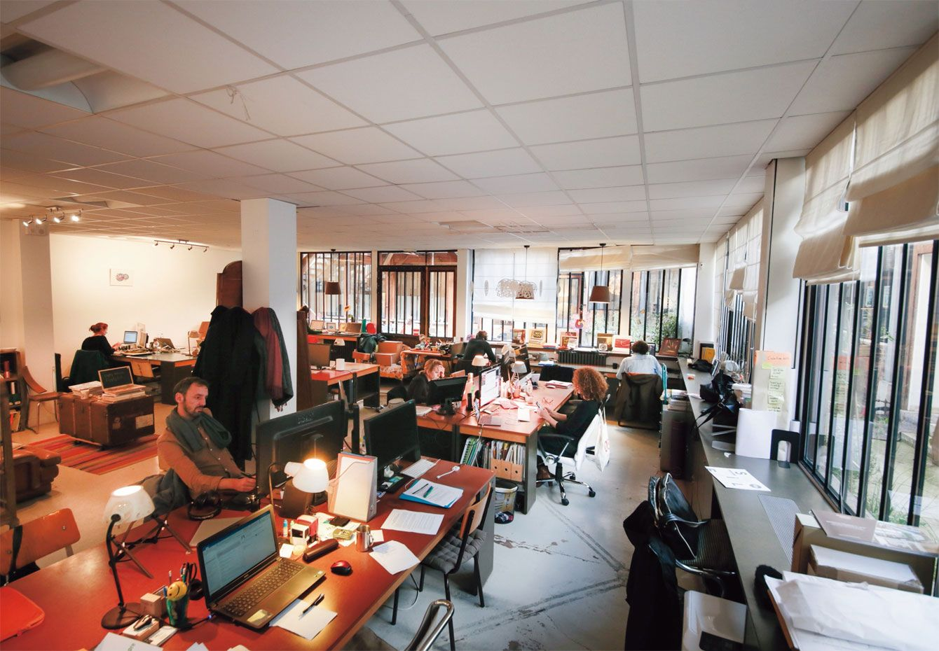 長期利用者のために13席、ノマド(短期利用者)に8席の割合で貸し出しているコワーキングスペース。窓からの自然光と間接照明が溶け合うパリらしい空間。
