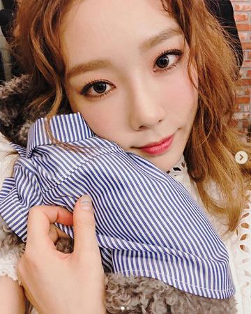 韓国ガールズグループ「Apink」メンバーのナウンが、先輩歌手テヨン(少女時代)のコンサートを訪れて花束のプレゼントを届けた。(写真提供:OSEN)
